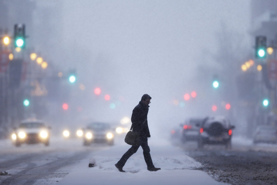 Photo - A man crosses Broad Street during a winter snowstorm Tuesday, Jan. 21, 2014, in Philadelphia. A swirling storm with the potential for more than a foot of snow clobbered the mid-Atlantic and the urban Northeast on Tuesday, grounding thousands of flights, closing government offices in the nation's capital and making a mess of the evening commute. (AP Photo/Matt Rourke)