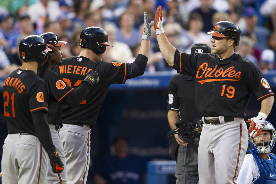 Photo - Baltimore Orioles' Chris Davis, right, is congratulated by Matt Wieters, center, Adam Jones, center left,  and Nick Markakis after hitting a three-run homer as Toronto Blue Jays catcher Josh Thole looks on during the sixth inning of a baseball action in Toronto on Friday, June 21, 2013. (AP Photo/The Canadian Press, Chris Young)