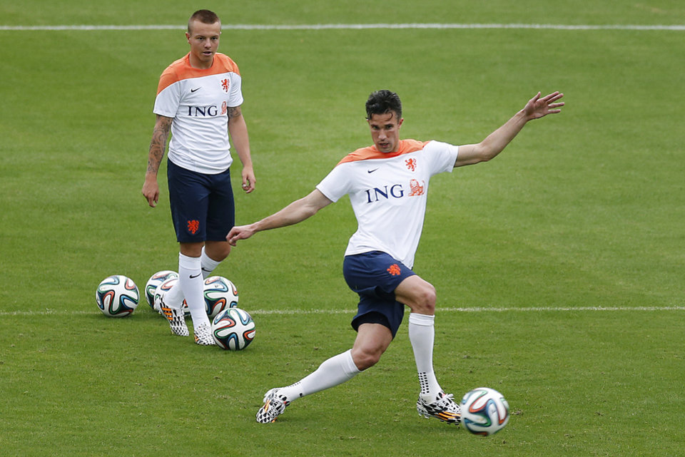 Photo - Robin van Persie, right, kicks the ball while Jordy Clasie, left, of the Netherlands waits his turn during a training session in Rio de Janeiro, Brazil, Tuesday, June 10, 2014.  The Netherlands play in group B of the 2014 soccer World Cup. (AP Photo/Wong Maye-E)