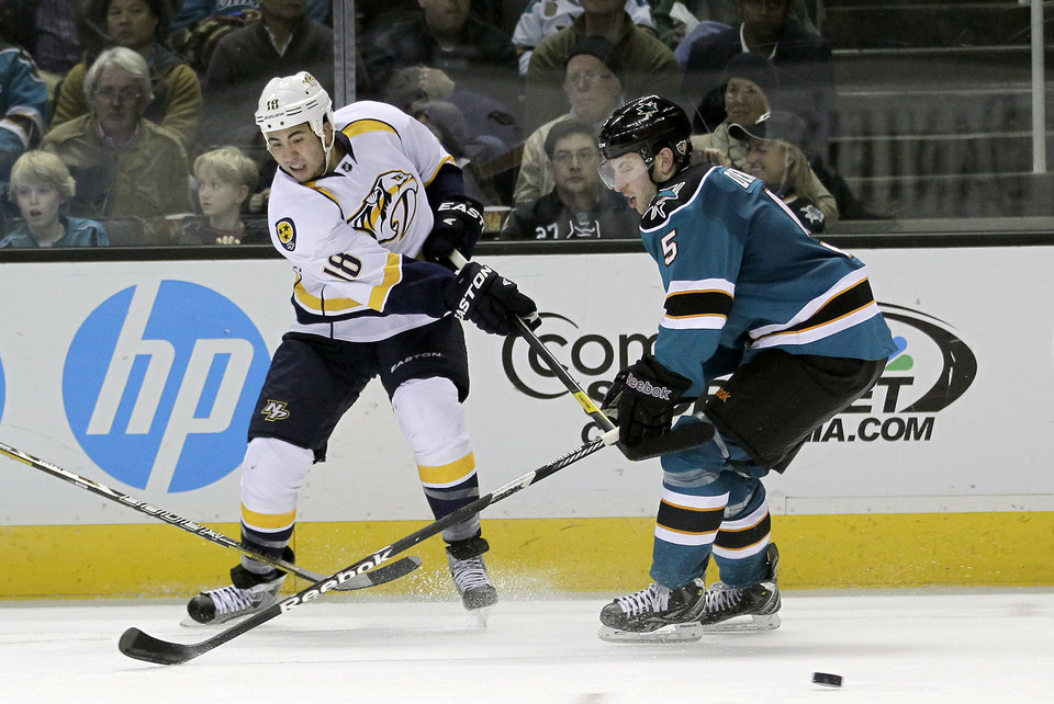 Nashville Predators right wing Brandon Yip (18) takes a shot at goal past San Jose Sharks Jason Demers (5) during the second period of an NHL hockey game in San Jose, Calif., on Saturday, Feb. 2, 2013. (AP Photo/Tony Avelar)