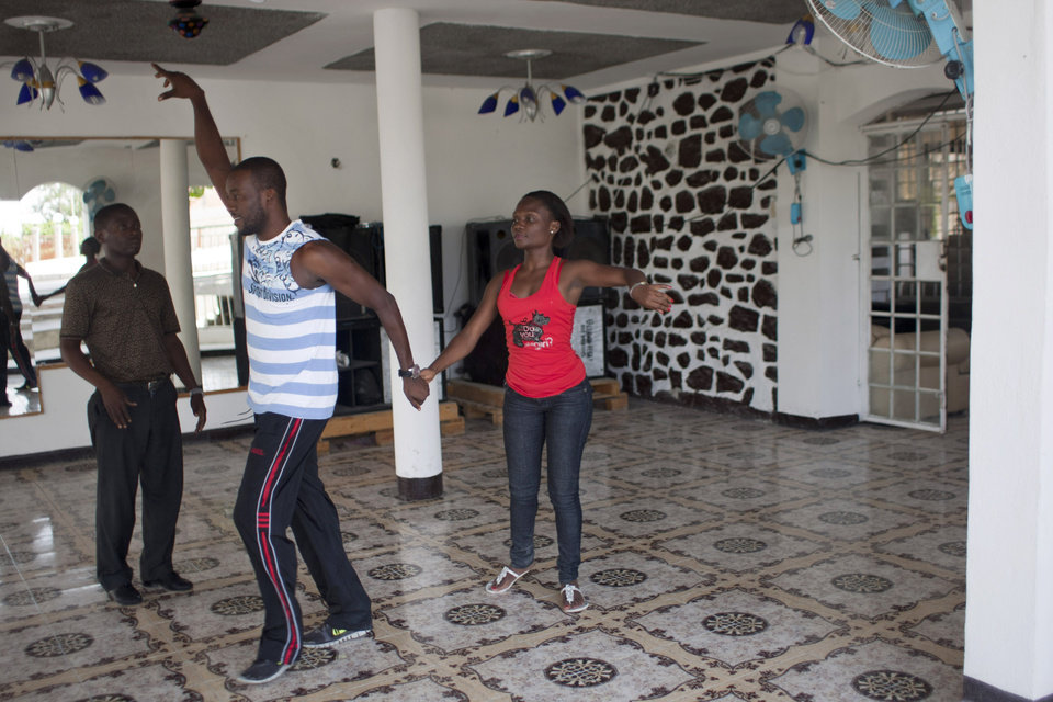 "Photo - In this Aug. 3, 2012 photo, professional dancer Georges Exantus, left, teaches a member of a professional dance group as they prepare for a concert in Port-au-Prince, Haiti. Exantus thought he'd never dance again. The earthquake three years ago in Haiti's capital flattened the apartment where he was living, where he spent three days trapped under a heap of jagged rubble. After friends dug him out, doctors amputated his right leg just below the knee. Israeli doctors and physical therapists who came to Haiti after the quake sent him to Israel for surgery and rehabilitation. Three years later, the 32-year-old professional dancer is back on the floor, spinning away as he does the salsa, cha-cha and samba. A prosthetic leg doesn't hold him back. ""As long as I'm living,"" Exantus says, ""I'm going to dance."" (AP Photo/Dieu Nalio Chery)"