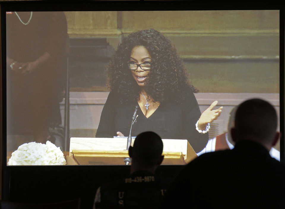 Photo - Media members watch a screen as Oprah Winfrey speaks during a memorial service for poet and author Maya Angelou at Wait Chapel. at Wake Forest University in Winston-Salem, N.C., Saturday, June 7, 2014. Former President Bill Clinton and Oprah Winfrey are joining First Lady Michelle Obama at the service. (AP Photo/Chuck Burton)