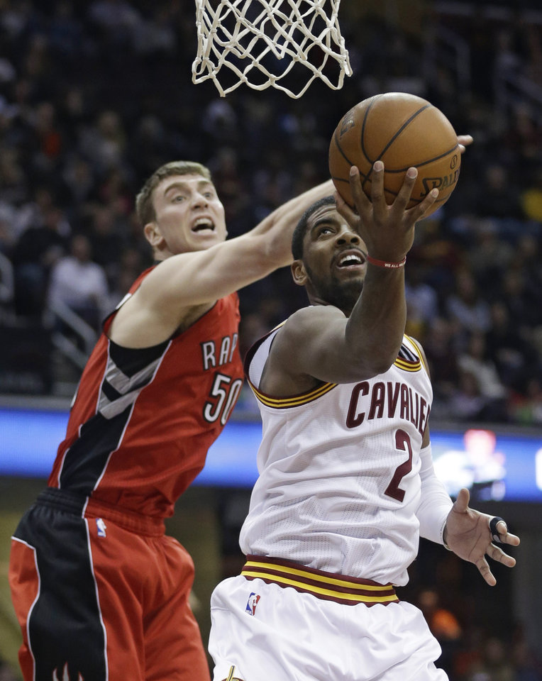 Photo - Cleveland Cavaliers' Kyrie Irving (2) shoots around Toronto Raptors' Tyler Hansbrough (50) during the second quarter of an NBA basketball game, Tuesday, Feb. 25, 2014, in Cleveland. (AP Photo/Tony Dejak)