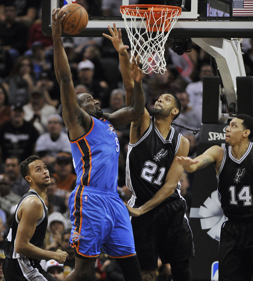 Photo - Oklahoma City Thunder center Kendrick Perkins (5) shoots against San Antonio Spurs forward Tim Duncan (21) during the first half an NBA basketball game, Dec. 25, 2014, in San Antonio. (AP Photo/Darren Abate)