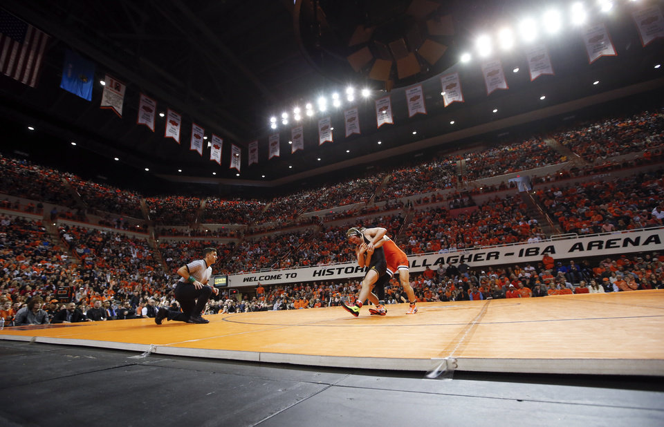 Photo - OSU's Preston Weigel and Iowa's Jacob Warner wrestle in a 197-pound match in front of a sold-out crowd during a college wrestling dual between the Oklahoma State Cowboys and the Iowa Hawkeyes at Gallagher-Iba Arena in Stillwater, Okla., Sunday, Feb. 24, 2019. OSU won 27-12. Photo by Nate Billings, The Oklahoman