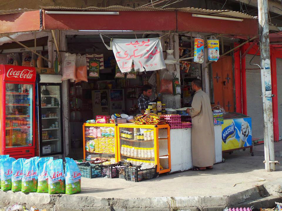 Photo - An Iraqi man shops for food at a market in the northern city of Mosul, Iraq, Friday, June 13, 2014. Iraqi officials say al-Qaida-inspired militants who this week seized much of the country's Sunni heartland have pushed into an ethnically mixed province northeast of Baghdad, capturing two towns there. The sign at the shop reads,