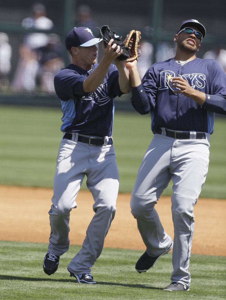 Photo - Tampa Bay Rays starting pitcher Jeremy Hellickson, left, and first baseman James Loney run into each other on a popup caught by Hellickson during the first inning of an exhibition spring training baseball game against the Detroit Tigers, Friday, March 29, 2013 in Lakeland, Fla. (AP Photo/Carlos Osorio)