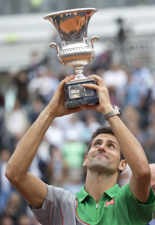 Photo - Serbia's Novak Djokovic holds up the trophy after defeating Spain's Rafael Nadald at the final match of the Italian Open tennis tournament, in Rome, Sunday, May 18, 2014. Novak Djokovic extended his recent dominance over Rafael Nadal by rallying for a 4-6, 6-3, 6-3 victory Sunday to win the Italian Open for the third time. (AP Photo/Andrew Medichini)