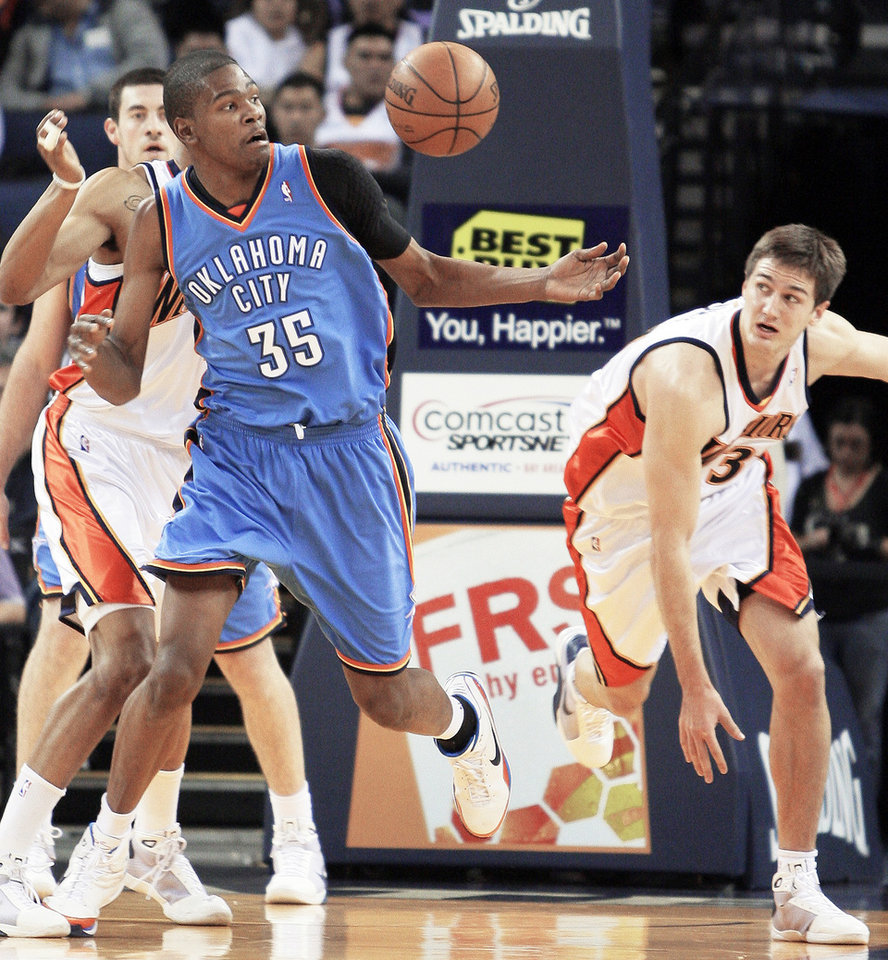 The Thunder's Kevin Durant, left, and Golden State's Rob Kurz, right, go after a loose ball on Wednesday. AP photo