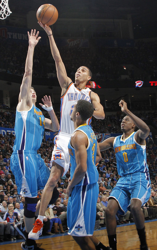 Oklahoma City Thunder's Kevin Martin (23) goes over the top of New Orleans Hornets' Jason Smith (14), Brian Roberts (22) and Al-Farouq Aminu (0) for a shot during the NBA basketball game between the Oklahoma CIty Thunder and the New Orleans Hornets at the Chesapeake Energy Arena on Wednesday, Dec. 12, 2012, in Oklahoma City, Okla.   Photo by Chris Landsberger, The Oklahoman