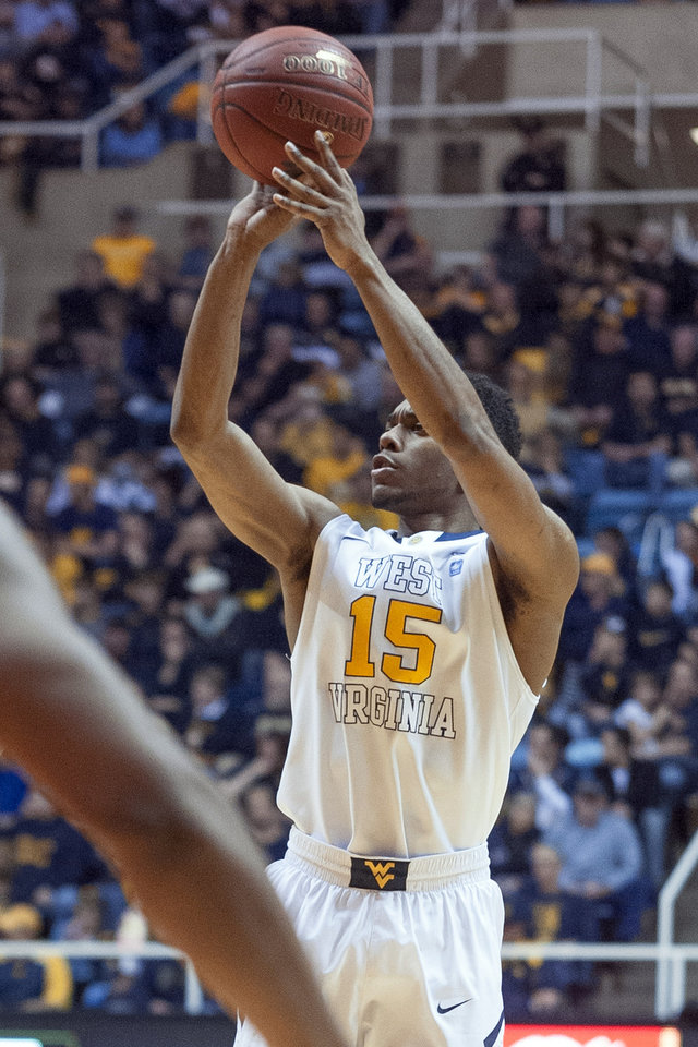 Photo - West Virginia's Terry Henderson (15) looks to shoot during the second half of an NCAA college basketball game against Oklahoma State, Saturday, Jan. 11, 2014, in Morgantown, W.Va. Oklahoma State won 73-72. (AP Photo/Andrew Ferguson)