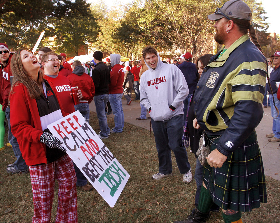 Garry Canaday, far right, is a lifelong Notre Dame fan. For his birthday, his best friend, Brook Bullock,Oklahoma City,  second from left, an avid Sooners fan, purchased tickets to Saturday's OU-Notre Dame football game. Canaday, who lives in Tonkawa, wore a kilt to the game. He said he is Scottish and the kilt represents his clan's tartan. At left is OU freshman Brittany Boren of Ft. Worth, who teased Canaday by showing him  the sign she made.  ESPN broadcast their weekly pre-game sports show, GameDay,  from the  the campus of the University of Oklahoma, Saturday morning, Oct. 27, 2012. The network's broadcast few is in Norman for the OU - Notre Dame football game Saturday night.  Several thousand OU fans and a smattering of Notre Dame supporters , many carrying homemade signs, crowded around the stage to watch the live broadcast.  Photo by Jim Beckel, The Oklahoman