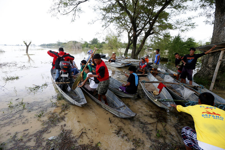 Photo - Commuters, unable to use the highway due to raging floodwaters from Typhoon Koppu, ride a boat to get to their destinations in La Paz township, Tarlac province, in northern Philippines Tuesday, Oct. 20, 2015. Slow-moving Typhoon Koppu blew ashore with fierce winds in the northeastern Philippines early Sunday, toppling trees and knocking out power and communications and forcing the evacuation of thousands of villagers. (AP Photo/Bullit Marquez)