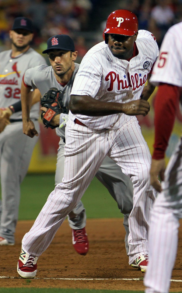 Photo - Philadelphia Phillies' Ryan Howard runs home to score on a hit by Carlos Ruiz as the St. Louis Cardinals' third baseman Matt Carpenter chases the ball in the third inning of a baseball game, Friday, Aug. 22, 2014, in Philadelphia. (AP Photo/Laurence Kesterson)