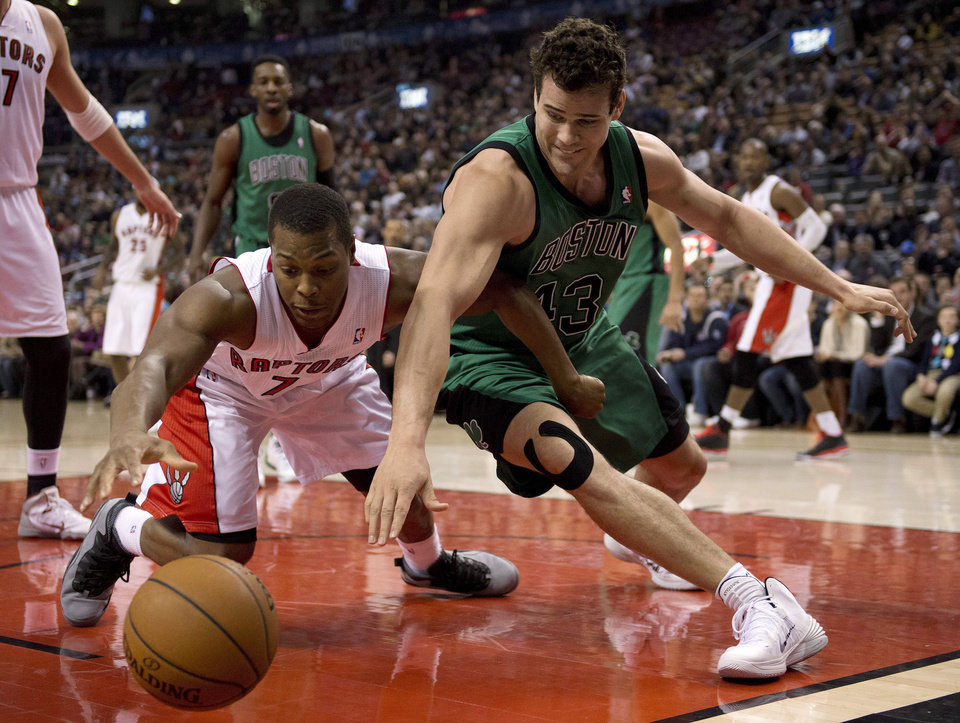 Photo - Toronto Raptors guard Kyle Lowry, left, and Boston Celtics forward Kris Humphries scramble for a loose ball during the first half of an NBA basketball game in Toronto on Friday, March 28, 2014. (AP Photo/The Canadian Press, Frank Gunn)