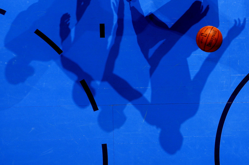 Photo - Shadows are cast as players watch the ball go towards the basket during the NBA basketball game between the Oklahoma City Thunder and the Cleveland Cavaliers at Chesapeake Energy Arena in Oklahoma City, Friday, March 9, 2012. Photo by Bryan Terry, The Oklahoman
