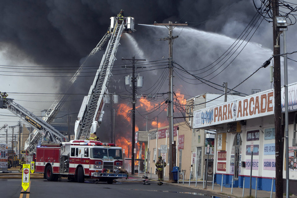 Photo - Firefighters battle a fire on the Seaside Heights, N.J. boardwalk Thursday, Sept. 12, 2013. The fire started in the vicinity of an ice cream shop and burned several blocks of boardwalk and businesses in a town that was still rebuilding from damage caused by Superstorm Sandy. (AP Photo/The Asbury Park Press, Bob Bielk)  NO SALES