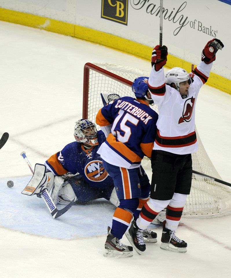 New Jersey Devils' Adam Henrique (14) celebrates after scoring a goal against New York Islanders goalie Evgeni Nabokov (20) in the first period of an NHL hockey game on Saturday, Dec. 28, 2013, in Uniondale, N.Y. (AP Photo/Kathy Kmonicek)