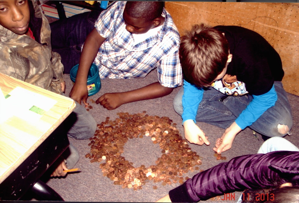 """Photo -  Students in Mary Beth Goff's class in Cairo, Ill., count pennies collected through their """"Pennies as Promise"""" project to memorialize children killed in the Holocaust. Photo provided   CH"""
