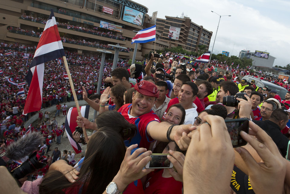 Photo - Costa Rica's President Luis Guillermo Solis, center, joins soccer fans celebrating their team's victory over Greece at a Brazil World Cup round of 16 game in San Jose, Costa Rica, Sunday, June 29, 2014. Costa Rica won a penalty shootout 5-3 after the match ended 1-1 following extra time. (AP Photo/Esteban Felix)