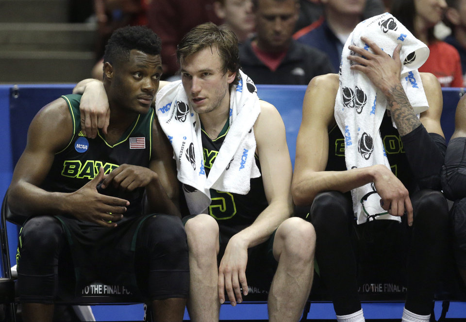 Photo - Baylor guard Brady Heslip, center, hugs a teammate as Isaiah Austin wipes his face with towel during the second half against Wisconsin in an NCAA men's college basketball tournament regional semifinal, Thursday, March 27, 2014, in Anaheim, Calif. Wisconsin won 69-52. (AP Photo/Jae C. Hong)