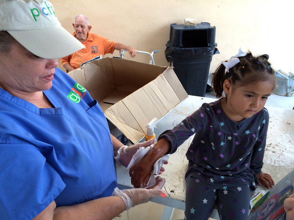 Photo -  A girl receives medical treatment by a volunteer working with People Caring for People, an Oklahoma City nonprofit. Photo provided.