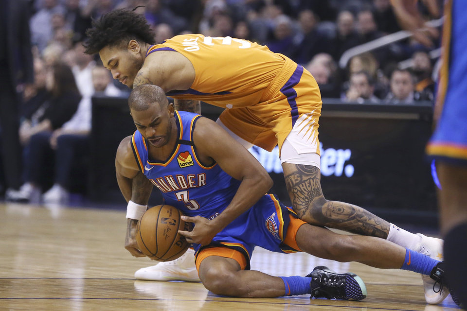 Photo - Oklahoma City Thunder guard Chris Paul (3) dives for a loose ball, beating Phoenix Suns forward Kelly Oubre Jr. (3) to it during the second half of an NBA basketball game Friday, Jan. 31, 2020, in Phoenix. The Thunder won 111-107. (AP Photo/Ross D. Franklin)