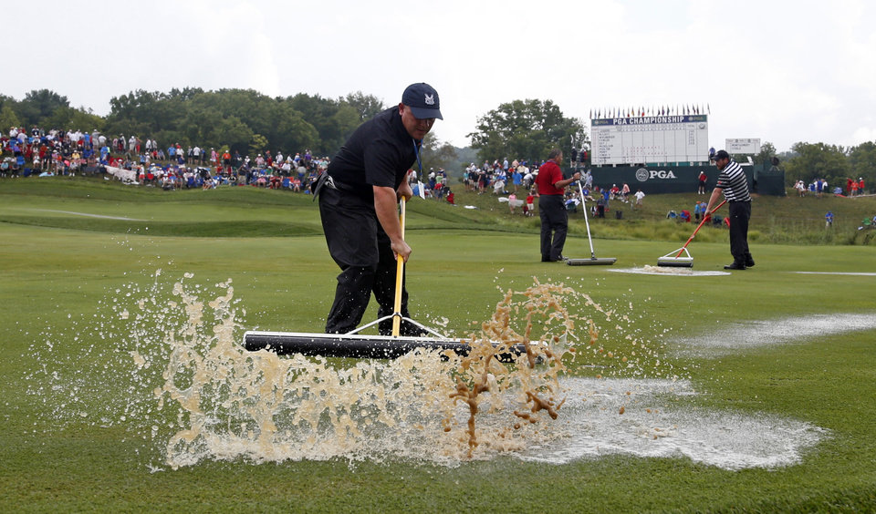 Photo - Course workers push rain water off the first hole during a weather delay in final round of the PGA Championship golf tournament at Valhalla Golf Club on Sunday, Aug. 10, 2014, in Louisville, Ky. (AP Photo/Mike Groll)