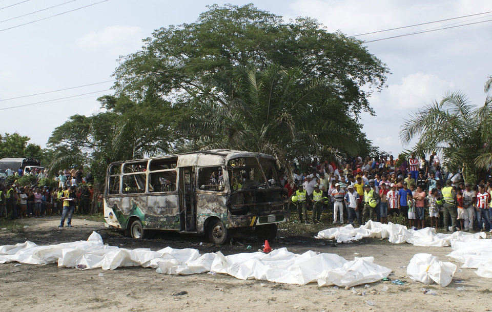Photo - People gather around a burnt bus and bags containing the remains of children who where killed when their bus caught fire in Fundacion, in northern Colombia, Sunday, May 18, 2014. Colombian authorities have detained the driver of the overcrowded bus that burned, killing 32 children, the local mayor said Monday. Luz Estella Duran, mayor of the village of Fundacion, said witness accounts suggest the driver may have left the vehicle running with the children on board when he descended from the bus to fill tank from a portable gas container. (AP Photo/Oscar Mejia, Hoy Diario del Magdalena)