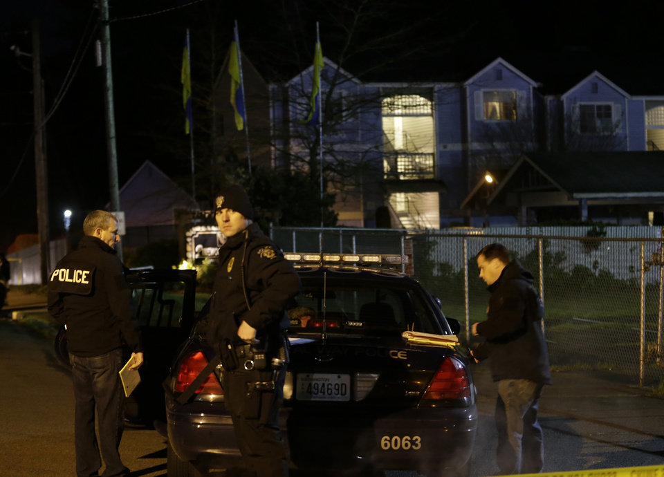 Photo - Police officers stand by their car at the scene of an overnight shooting that left five people dead, Monday, April 22, 2013, at the Pinewood Village apartment complex in Federal Way, Wash. (AP Photo/Ted S. Warren)