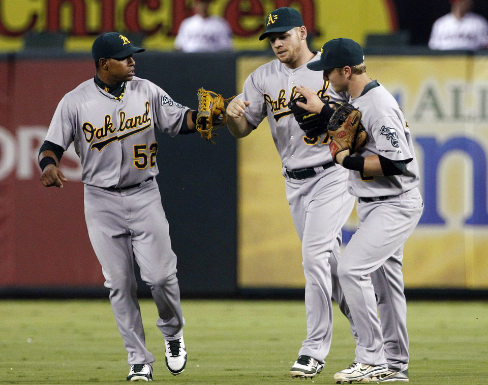 Photo -   Oakland Athletics' Yoenis Cespedes (52) and Cliff Pennington, right, congratulate right fielder Brandon Moss, center, on his catch against the wall on a bases-loaded fly ball from Texas Rangers' Elvis Andrus in the seventh inning of a baseball game, Tuesday, Sept. 25, 2012, in Arlington, Texas. The Athletics won 3-2 in the 10th inning. (AP Photo/Tony Gutierrez)