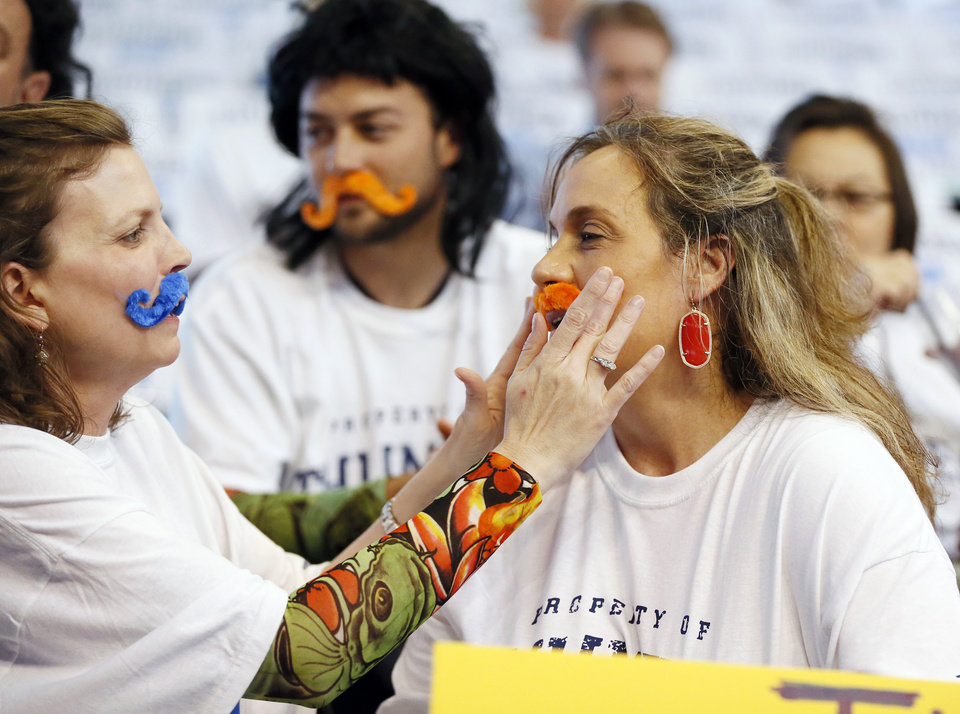Photo -   Above:  Brenda Wright helps Stephanie Ballard put on a mustache before Game 4 of the Western Conference semifinals between the Oklahoma City Thunder and the San Antonio Spurs earlier this month.