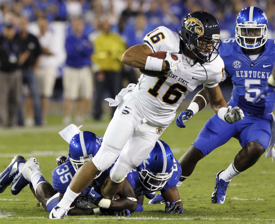 Photo -   Kent State's Sam Miller (16) tries to escape Kentucky's Cartier Rice (35), Eric Dixon and Ashely Lowery (5) during the second quarter of an NCAA college football game in Lexington, Ky., Saturday, Sept. 8, 2012. (AP Photo/James Crisp)