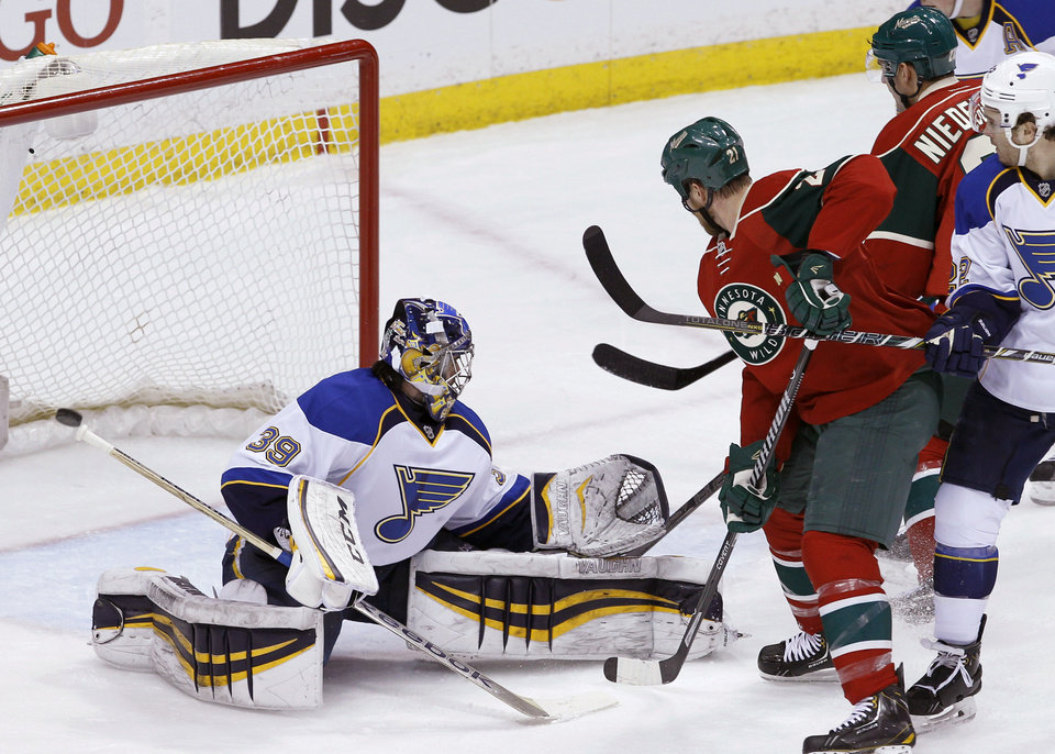 Photo - Minnesota Wild center Kyle Brodziak (21) and St. Louis Blues defenseman Kevin Shattenkirk, right, watch as a shot by Wild right wing Nino Niederreiter, rear, of Switzerland, gets past Blues goalie Ryan Miller (39) during the first period of an NHL hockey game in St. Paul, Minn., Thursday, April 10, 2014. (AP Photo/Ann Heisenfelt)