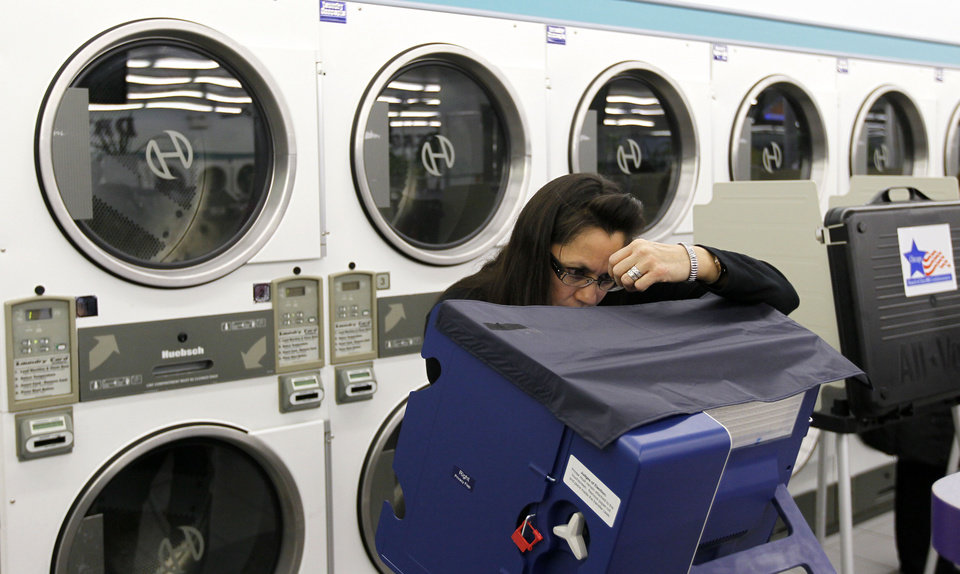 Photo -   Leslie Fabian concentrates as she votes electronically inside at the 24-hour Su Nueva Laundromat in Chicago's 13th Ward Tuesday, Nov. 6, 2012, in Chicago. (AP Photo/Charles Rex Arbogast)