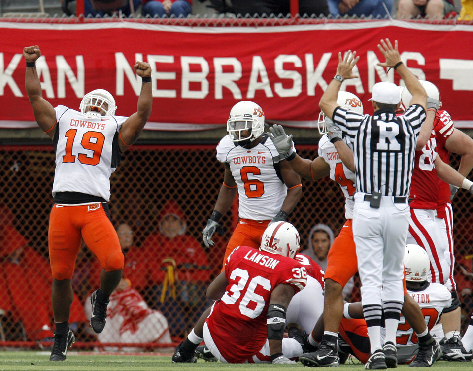Photo - CELEBRATE, CELEBRATION: OSU's Jeremy Nethon (19) celebrates a stop of Nebraska's Quentin Castille, not pictured, on fourth down in the second quarter during the college football game between Oklahoma State University (OSU) and the University of Nebraska (NU) at Memorial Stadium in Lincoln, Neb., Saturday, October 13, 2007. By Nate Billings, The Oklahoman  ORG XMIT: KOD
