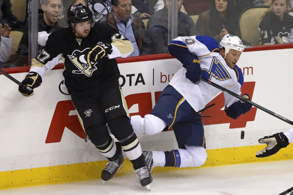 Photo - Pittsburgh Penguins' Simon Despres (47) collides with St. Louis Blues' Brenden Morrow (10) in the first period of an NHL hockey game in Pittsburgh, Sunday, March 23, 2014. (AP Photo/Gene J. Puskar)