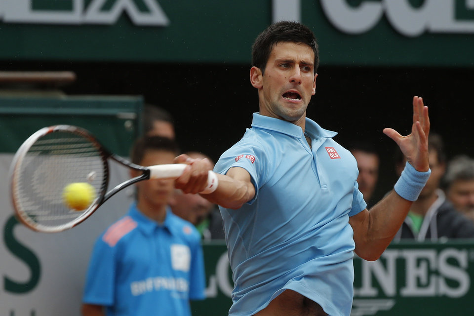 Photo - Serbia's Novak Djokovic returns the ball during the first round match of the French Open tennis tournament against Portugal's Joao Sousa at the Roland Garros stadium, in Paris, France, Monday, May 26, 2014. (AP Photo/Michel Euler)