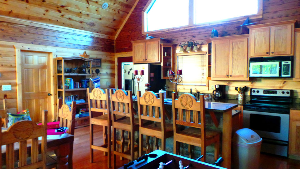 Photo - The kitchen at Bella Lodge, available to rent through Broken Bow Cabin Lodging, has granite countertops and plenty of seating for guests. PHOTO BY LILLIE-BETH BRINKMAN, THE OKLAHOMAN
