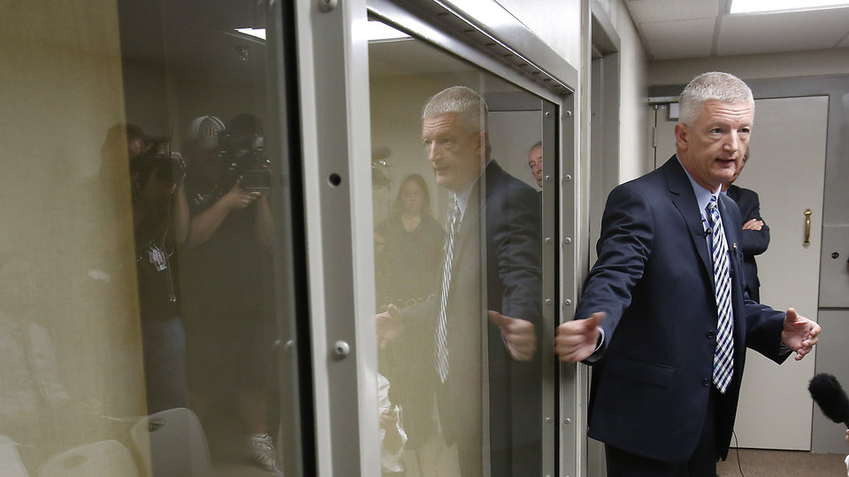 Photo - Administrator of Field Operations Scott Crow demonstrates the new glass in the viewing window during a tour of the new execution chamber at the Oklahoma State Penitentiary in McAlester, October 9, 2014. Photo by David McDaniel