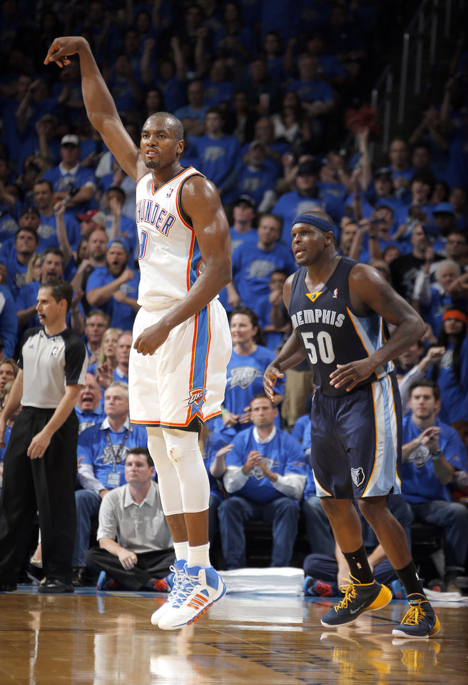 Photo - Oklahoma City's Serge Ibaka (9) reacts after making a 3-point basket in front of Memphis' Zach Randolph (50) during Game 1 in the first round of the NBA playoffs between the Oklahoma City Thunder and the Memphis Grizzlies at Chesapeake Energy Arena in Oklahoma City, Saturday, April 19, 2014. Photo by Sarah Phipps, The Oklahoman