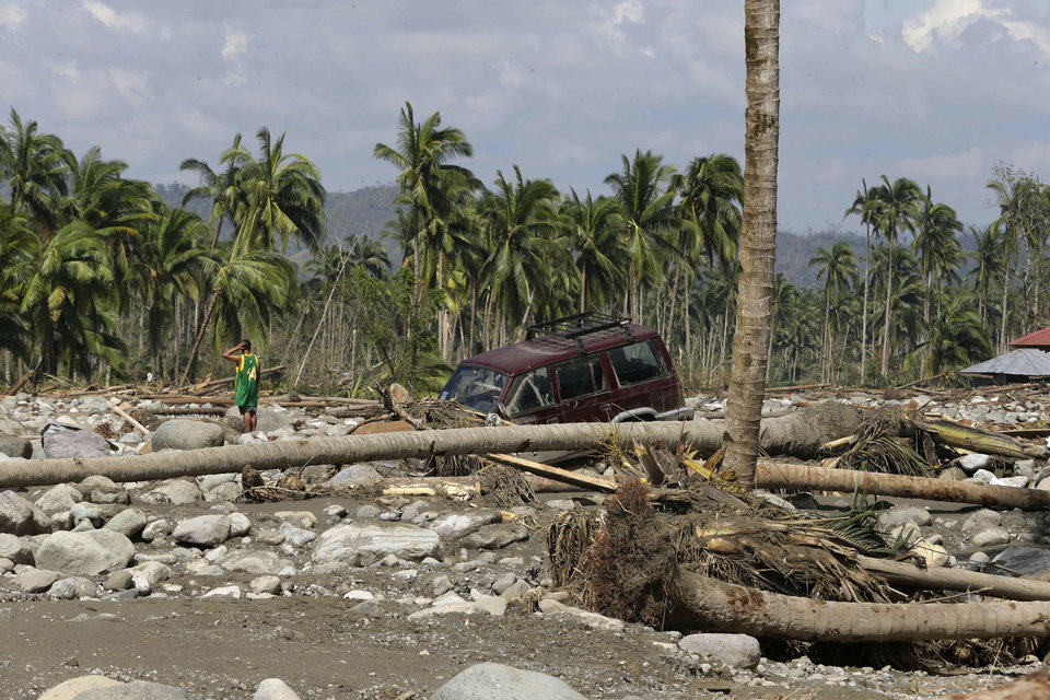 A resident searches for victims of Tuesday's devastating storm in New Bataan township, Compostela Valley in the southern Philippines Thursday, Dec. 6, 2012. The powerful typhoon that washed away emergency shelters, a military camp and possibly entire families in the southern Philippines has killed hundreds of people with nearly 400 missing, authorities said Thursday. (AP Photo/Bullit Marquez)