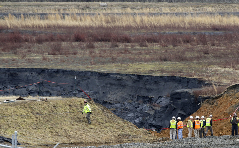 Photo - FILE - In a Wednesday, Feb. 5, 2014 file photo, Duke Energy engineers and contractors survey the site of a coal ash spill at the Dan River Power Plant in Eden, N.C., as state and federal environmental officials continued their investigations of the spill into the river. North Carolina regulators said Friday, March 21, 2014, that they have asked a judge to withdraw a proposed settlement that would have allowed Duke Energy to resolve environmental violations by paying a $99,000 fine with no requirement that the $50 billion company clean up its pollution. (AP Photo/Gerry Broome, File)