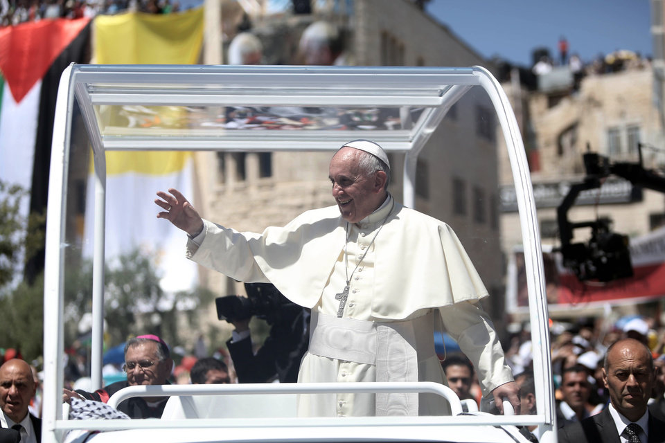 Photo - Pope Francis waves to people upon his arrival at the Manger Square, next the Nativity Church in the West Bank town of Bethlehem on Sunday, May 25, 2014. Francis called the Israeli-Palestinian stalemate