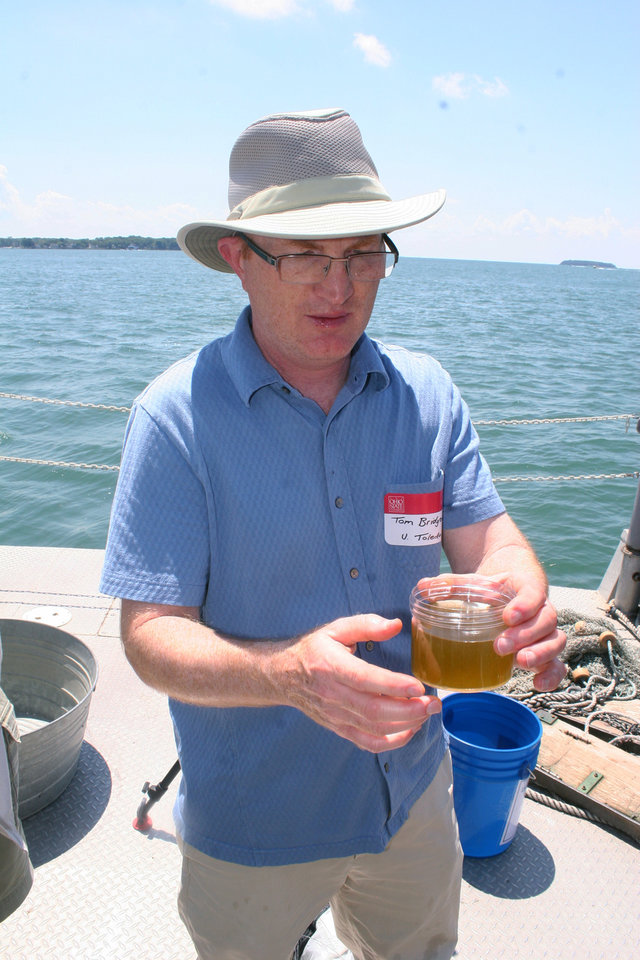 Photo - In this July 10, 2014 photo, Tom Bridgeman, University of Toledo algae researcher, examines a water sample drawn from Lake Erie aboard Ohio State Universities research vessel. Scientists gathered at OSU's Stone Laboratory near Put-In-Bay, Ohio, to discuss the 2014 algae forecast for Western Lake Erie. Ohio Gov. John Kasich declared a state of emergency in northwest Ohio, where about 400,000 people are being warned not to drink the water on Saturday, Aug. 2, 2014. Officials issued the warning Saturday after tests revealed the presence of a toxin possibly from algae on Lake Erie. (AP Photo/The Blade, Tom Henry)  MANDATORY CREDIT; MAGS OUT; NO SALES; TV OUT; SENTINEL-TRIBUNE OUT; MONROE EVENING NEWS OUT; TOLEDO FREE PRESS OUT