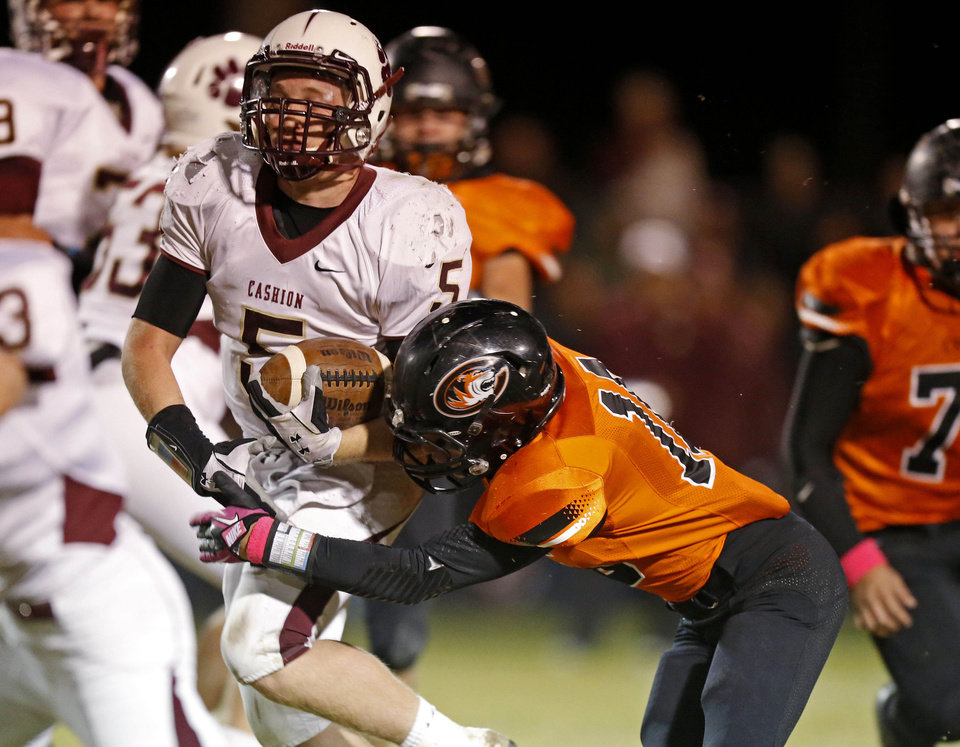 Cashion\'s Grant Quast fights off Crescent\'s Devon Bledsoe during a high school football game between Cashion and Crescent in Crescent, Okla., Thursday, Oct. 18, 2012. Photo by Bryan Terry, The Oklahoman