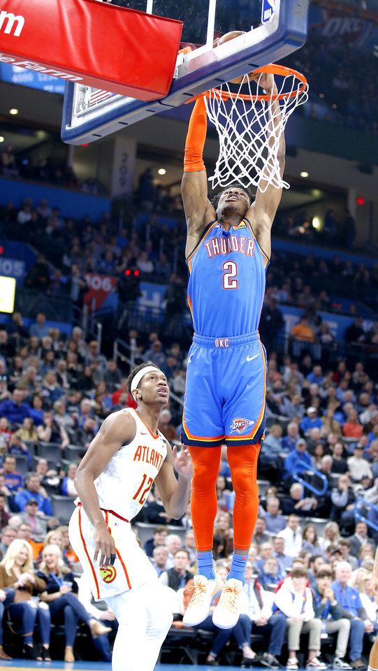 Photo - Oklahoma City's Shai Gilgeous-Alexander (2) dunks the ball in front of Atlanta's De'Andre Hunter (12) during the NBA basketball game between the Oklahoma City Thunder and the Atlanta Hawks at the Chesapeake Energy Arena in Oklahoma City,Friday, Jan. 24, 2020.  [Sarah Phipps/The Oklahoman]