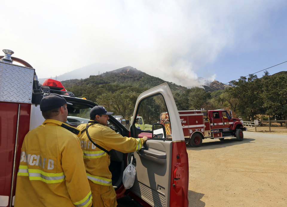 Photo - Capt. Jed Matcham, left, and firefighter Richard Netro, of the Benicia Fire Department monitor the Mount Diablo Fire on Monday, Sept. 9, 2013, in Clayton, Calif. A wildfire burning outside Mount Diablo State Park has forced dozens of residents and animals to evacuate Monday. (AP Photo/Marcio Jose Sanchez)