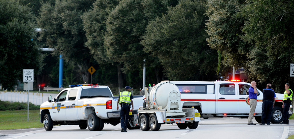 Photo - Police block the road to the Jacksonville International Airport terminal as the bomb disposal unit drives by on the right Tuesday, Oct. 1, 2013, in Jacksonville, Fla. The airport was evacuated after authorities found two suspicious packages. (AP Photo/The Florida Times-Union, Bruce Lipsky)