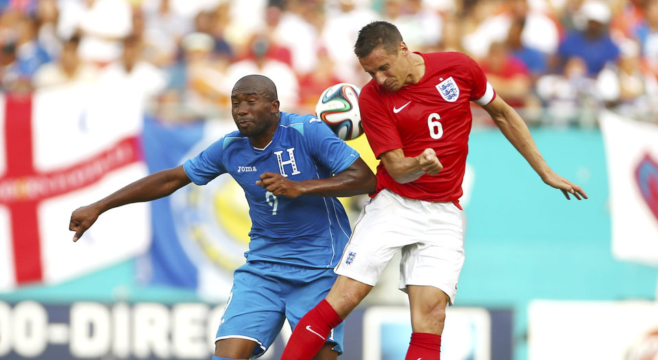 Photo - Honduras' Jerry Palacios (9) and England's Phil Jagielka (6) battle for a head ball during the second half of a friendly soccer match in Miami Gardens, Fla., Saturday, June 7, 2014. The game ended 0-0. ( AP Photo/J Pat Carter)